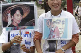 In this Nov. 12, 2010 photo, supporters of Myanmar's pro-democracy leader Aung San Suu Kyi hold portraits of their detained leader outside her National League for Democracy party in Rangoon, Burma