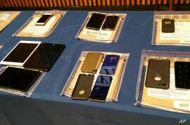 A collection of Apple iPhones and iPads fill a table during a news conference at New York City Police Headquarters, Feb. 18, 2016.  Police and prosecutors in New York City said Thursday that the top-notch encryption technology on Apple mobile phones