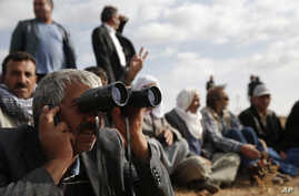 People gather on a hilltop on the outskirts of Suruc, at the Turkey-Syria border, to watch fighting between Syrian Kurds and the militants of Islamic State group in Kobani, Syria, Oct. 15, 2014.