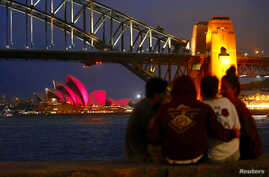 A group of people sit on a stone wall in front of the Sydney Opera House as it is illuminated in pink lights to mark the marriage equality bill being passed this week by the Australian parliament in Sydney, Australia, Dec. 8, 2017.