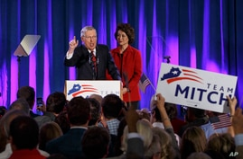 Republican Senate Minority Leader Mitch McConnell of Kentucky, joined by his wife, former Labor Secretary Elaine Chao, celebrates with supporters at an election night party in Louisville, Nov. 4, 2014.
