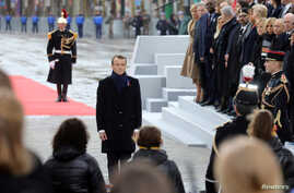 French President Emmanuel Macron pays his respects by the Tomb of the Unknown Soldier during a commemoration ceremony for Armistice Day, 100 years after the end of the World War I, at the Arc de Triomphe, in Paris, Nov. 11, 2018.