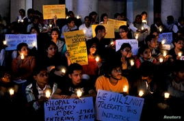 Activists from Bengaluru Solidarity Group, a social group, hold candles and placards during a vigil to commemorate the 30th anniversary of Bhopal gas tragedy, in the southern Indian city of Bengaluru, previously known as Bangalore, December 2, 2014.