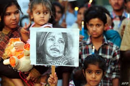An Indian child poses with a placard as demonstrators participate in a protest in Allahabad, April 23, 2013, following the rape of a five-year old girl in New Delhi.