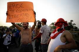 """A protester holds a sign toward Venezuelan National Guards that reads in Spanish """"Hero. We're waiting for you. Freedom. Let's go Venezuela."""" at the Simon Bolivar International Bridge where guardsmen are blocking the entry of U.S.-supplied aid, during"""
