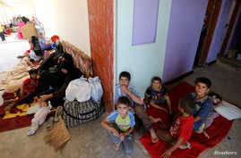 Civilians who fled their homes due to the clashes on the outskirts of Falluja, gather in the town of Garma, Iraq, May 30, 2016.