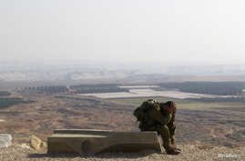 An Israeli soldier rests after completing a 45 km march in the Jordan Valley, Jan. 2, 2014. The Jordan Valley is part of the West Bank and borders Jordan.
