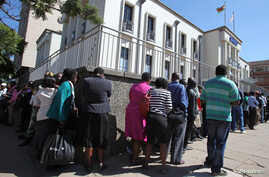 Residents queue to withdraw cash at a local bank in Harare, Zimbabwe, May 5, 2016.