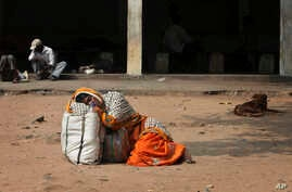An Indian attendant of a patient suspected with swine flu virus rests on the ground in the premises of Gandhi Hospital in Hyderabad, India, Wednesday, Jan. 21, 2015. According to local reports, nine people died of the flu at the state-run hospital.