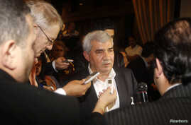 Leading Syrian dissident Riad Seif (C) speaks to the media at the meeting of the General Assembly of the Syrian National Council in Doha, November 8, 2012.