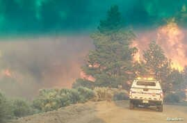 FILE - Flames rise from a treeline near an emergency vehicle during efforts to contain the Spring Fire in Costilla County, Colorado, June 27, 2018.