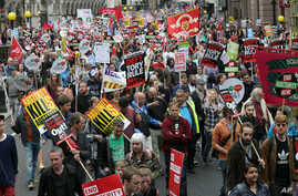 Demonstrators hold placards as they march during a protest against the Conservative Government and it's austerity policies in London, June 20, 2015.