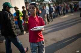 Dennis Mauricio Suarez, 12, from Honduras, eats breakfast at the Jesus Martinez stadium in Mexico City, Nov. 7, 2018.