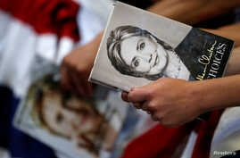 """FILE - A supporter holds the book """"Hard Choices"""" by Democratic U.S. presidential candidate Hillary Clinton before she speaks at a campaign event at the North Carolina State Fairgrounds in Raleigh, North Carolina, June 22, 2016."""