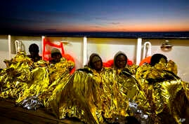 Sub-Saharan migrants cover themselves with a heating blanket at the deck of the Golfo Azzurro boat after been rescued from a rubber boat by members of Proactive Open Arms NGO, at the Mediterranean sea, about 24 miles north of Sabratha, Libya, Jan. 27