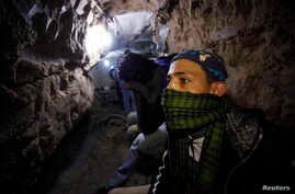 Palestinian worker moves goods through a smuggling tunnel between the Gaza Strip and the Egyptian Sinai Febryary 19, 2013. The tunnel was flooded by Egyptian forces last month to stop the smubbling.UNNELS/EGYPT