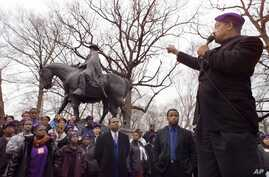 FILE - The Rev. Jesse Jackson gestures toward a statue of Confederate Gen. Robert E. Lee during a rally.