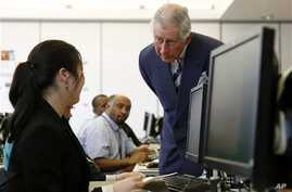 Britain's Prince Charles talks to a computer student at the Carlos Rosario International Public Charter School for Adults in Washington, Thursday, March 19, 2015. The school has more than 2,900 students and is tailored to meet the needs of the local