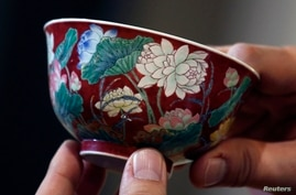 "A magnificent Ruby-Ground Falangcai ""Double-Lotus"" Bowl Blue Enamel Yuzhi Mark and Period of Kangxi is shown after being sold for HK$74 million ($9.5 million) at Sotheby's Spring Sales in Hong Kong, April 8, 2013."