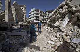 Syrian children walk between destroyed buildings in the old city of Homs, Syria, Feb. 26, 2016.