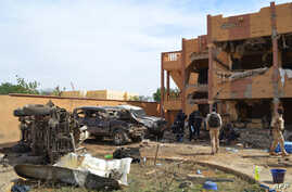 Malian firefighters and soldiers walk beside a destroyed building and burnt cars after a suicide car bomb attack overnight, which killed three people, in Gao, Nov. 13, 2018.