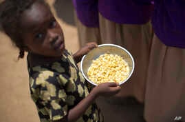 A child holds a bowl of food given out during a food distribution in the drought-affected village of Bandarero, near Moyale town on the Ethiopian border, in northern Kenya, March 3, 2017.