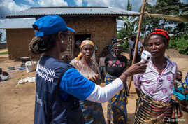 Dr. Marie-Roseline Darnycka Bélizaire, World Health Organization (WHO) Epidemiology Team Lead, talks to women as part of Ebola contact tracing, in Mangina, Democratic Republic of Congo, Aug. 26, 2018.