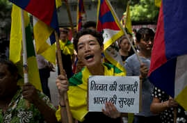 Exile Tibetans shout slogans during a protest to show support with India in the Doklam standoff in New Delhi, Aug. 11, 2017.