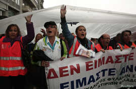 Protesters hold a plastic sheet to protect themselves from the rain as they take part in an anti-austerity rally during a 24-hour general labour strike in Athens November 6, 2013. Thousands of striking Greek workers marched to parliament in pouring r