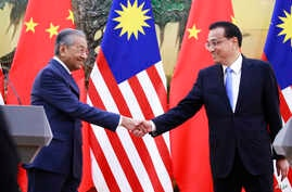Malaysian Prime Minister Mahathir Mohamad, left, shakes hands with his Chinese counterpart Li Keqiang at the end of a press conference at the Great Hall of the People in Beijing,  Aug. 20, 2018.