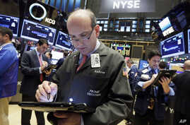 Trader Andrew Silverman, center, works on the floor of the New York Stock Exchange, Dec. 2, 2015.