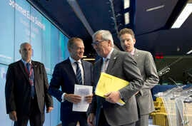From second left, European Council President Donald Tusk, European Commission President Jean-Claude Juncker and Dutch Finance Minister Jeroen Dijsselbloem speak with each other during a media conference after a meeting of eurozone heads of state at t