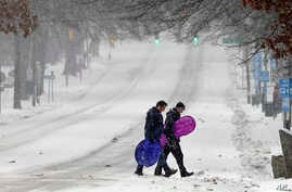 Pedestrians cross a snowy Franklin Street in Chapel Hill, N.C., Jan. 7, 2017, as a winter storm blankets the area with sleet and snow. Some parts of North Carolina received snow, others got rain and sleet.