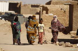 Indigenous Sahrawi women walk through Al Smara desert refugee camp in Tindouf, southern Algeria, March 4, 2016.
