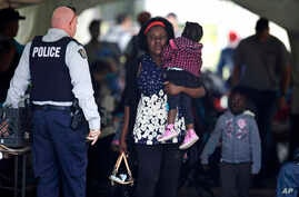A woman carries a child out of a makeshift police station after crossing illegally into Canada, from the end of Roxham Road in Champlain, New York, in Saint-Bernard-de-Lacolle, Quebec, Aug. 7, 2017.