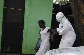 A health worker brings a woman suspected of having contracted the Ebola virus to an ambulance in Monrovia, Liberia, Sept. 15, 2014.