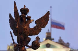 A sculpture of a double-headed eagle, a national symbol of Russia, is seen in front of a Russian national flag flying at half-mast on the roof of the State Hermitage Museum in St. Petersburg, Nov. 1, 2015.