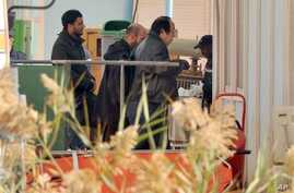 An unidentified person right, is followed by Algerian officials as they enter a morgue in Ain Amenas Algeria Monday, Jan. 21, 2013,  where the bodies of the persons killed during the hostage situation at the gas plant in Ain Amenas,. At least 81 peop