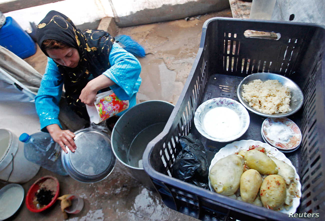 A Syrian refugee washes dishes at a camp in Tyre, Lebanon, Jan. 31, 2013.