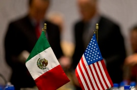 FILE - Miniature national flags representing Mexico and the United States stand side by side during trade discussions in Mexico City, July 29, 2014.