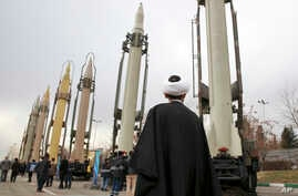 An Iranian cleric looks at domestically built surface-to-surface missiles at a military show marking  the 40th anniversary of Iran's Islamic Revolution that toppled the U.S.-backed shah, at Imam Khomeini Grand Mosque, in Tehran, Iran, Feb. 3, 2019.