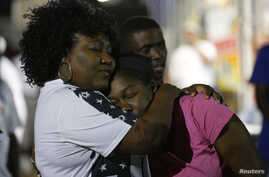 FILE - Community members embrace during a vigil at the Triple S Food Mart after the U.S. Justice Department announced it would not charge two police officers in the 2016 fatal shooting of Alton Sterling, in Baton Rouge, La., May 2, 2017. Baton Rouge'