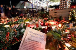 People stay in front of candles close to a Christmas market beside the Kaiser Wilhelm memorial church in Berlin, Germany, Dec. 21, 2016, two days after a truck ran into a crowded Christmas market there, killed several people and injuring dozens.