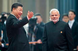 Chinese President Xi Jinping, left, welcomes Indian Prime Minister Narendra Modi for a meeting at the Shanghai Cooperation Organization (SCO) Summit in Qingdao in eastern China's Shandong Province, June 10, 2018.
