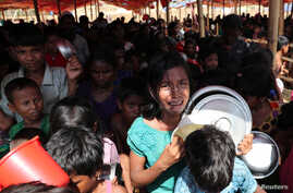A Rohingya refugee girl cries as children push each other while standing in the queue to collect food in the Palongkhali makeshift refugee camp in Cox's Bazar, Bangladesh, Nov. 7, 2017.
