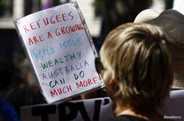 """FILE - Protesters hold placards at a """"Stand up for Refugees"""" rally held in central Sydney, Oct. 11, 2014."""