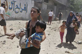 Palestinians run following what police said was an Israeli air strike on a house in Gaza City, July 9, 2014.