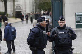 Policemen guard the entrance of the Pere Lachaise cemetery during the funeral of French cartoonist Georges Wolinski, in Paris, Thursday, Jan. 15, 2015. The country is tense since 20 people, including three gunmen, were killed in last week's rampage.