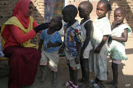 A social worker gives polio drops to children from al-Muniera village in Madani, FILE November 18, 2007.