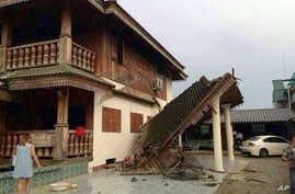 A woman looks at a partly damaged house following an earthquake in Chiang Rai province, northern Thailand, on May 5, 2014.
